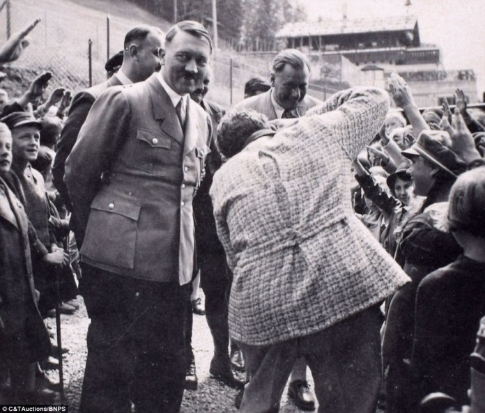 Another image shows him smiling in front of a crowd of children who are saluting him outside the Berghof building in the Bavarian mountains