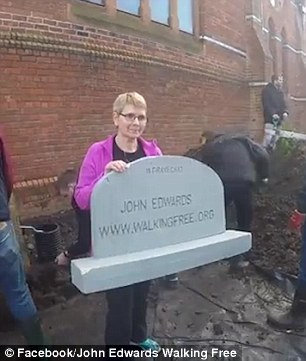 His wife of 20 years, Trish, posed for the cameras with a mock tombstone while he was buried on the site earlier today