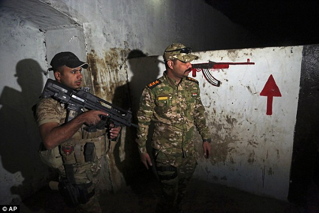 Iraqi security forces inspect a recently discovered tunnel that had been used by Islamic State militants as a training camp, in western Mosul, Iraq on Wednesday, March 1. 2017