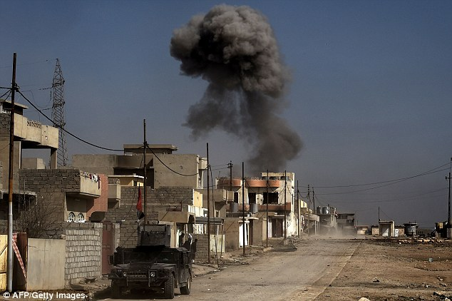 Syrian government forces, Turkish troops and their Syrian militia allies, and US-backed Kurdish forces all have their eye on Raqqa. Pictured: Smoke billows as Iraqi forces hold a position on a street in Mosul on March 1