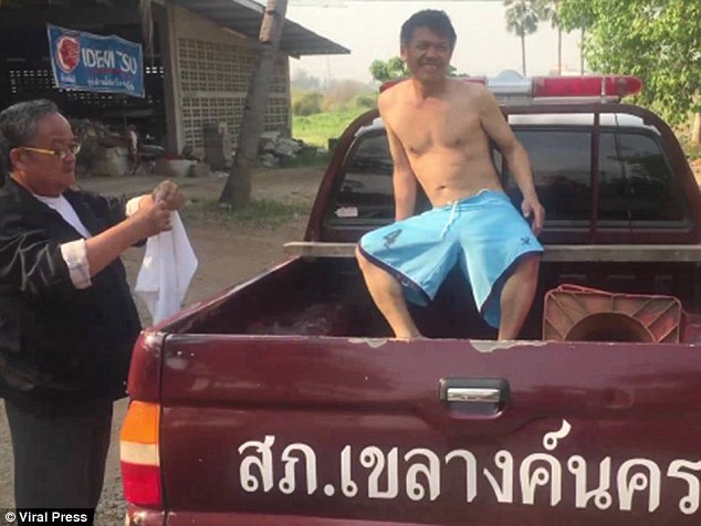 The smiling man was given a pair of shorts to wear by locals before he was taken away