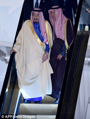 King Salman (left) gets off the plane in Japan