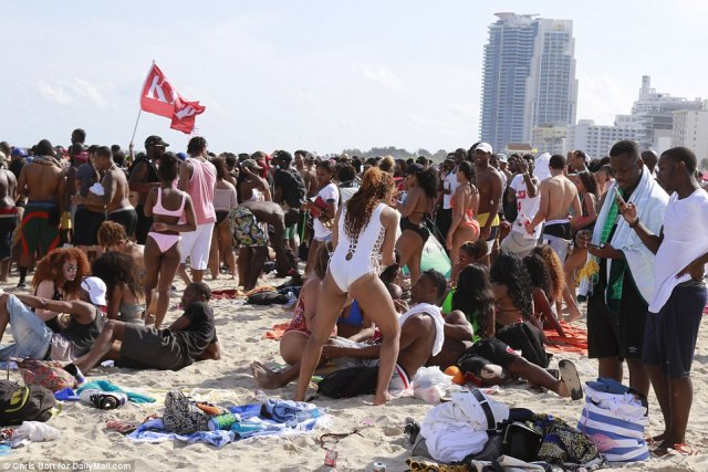 Despite alcohol being banned on the beach, huge crowds of Spring Breakers formed - some raising fraternity flags - to party on the sand