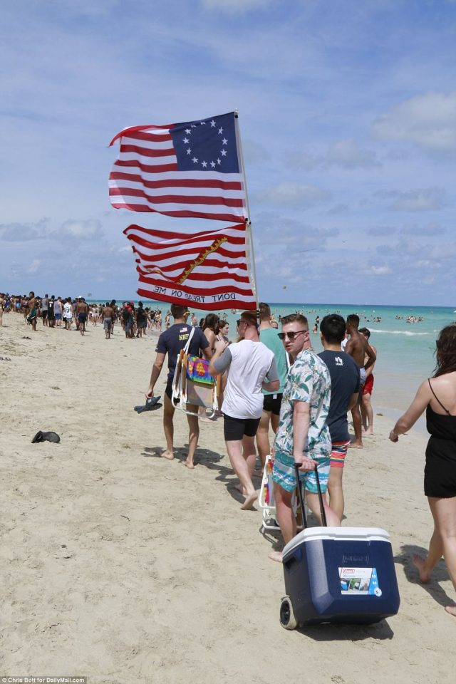 A group of men, carrying a 'Don't Tread on Me' flag and pulling coolers, looked determined to take on the beach - while the partier in the back looked a bit wary