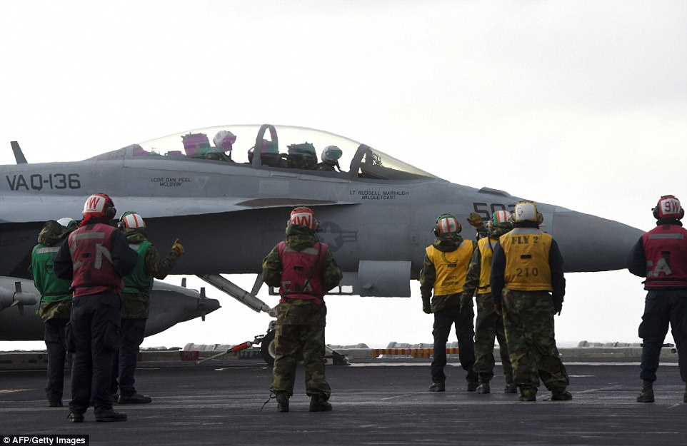 US Navy crew members stand by an EA-18G Growler electronic warfare aircraft on the deck of the Nimitz-class aircraft carrier USS Carl Vinson