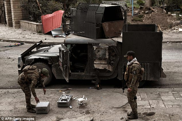 Two Iraqi soldiers prepare the drone on the street next to a heavily-armoured vehicle for the test flight
