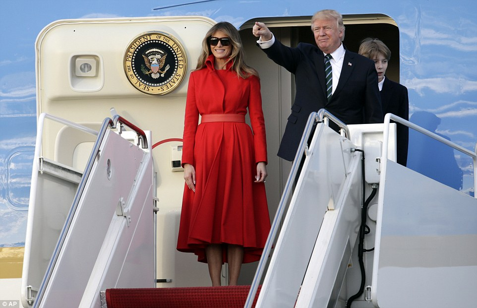 President Donald Trump points from Air Force One with First Lady Melania and son Barron after arriving at the Palm Beach International Airport