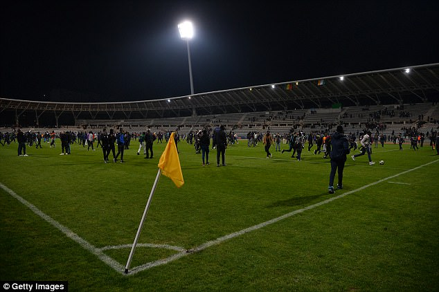 Dozens of fans stand on the field of play with one kicking a ball after the game is abandoned
