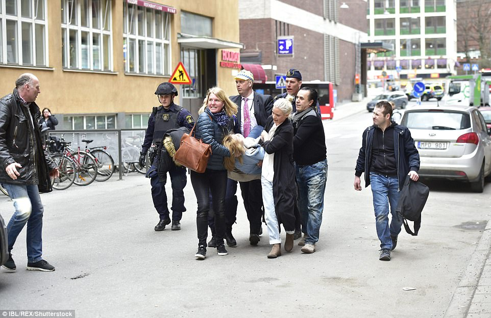 An injured person was seen being carried from the scene by a group of bystanders
