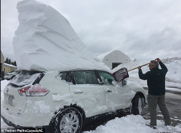 The real snowmaggedon: A man is seen shoveling out his car, but it seems he still has massive block a snow to get through