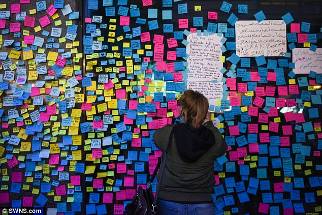 Messages of peace: A woman places a post-it note on an already covered window of a shop in Stockholm, Sweden. Among the dead is Chris Bevington, a Briton who worked for Spotify