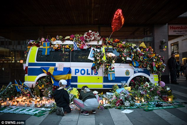 Saddest display: In a stunning but heartbreakingly sad gesture of remembrance, a police van was garlanded in flowers, Swedish flags, candles and balloons