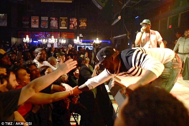 Trying to pull back his arm: The rapper was performing with The Lox At Baltimore Soundstage when he tried to shake the hand of a fan in the crowd