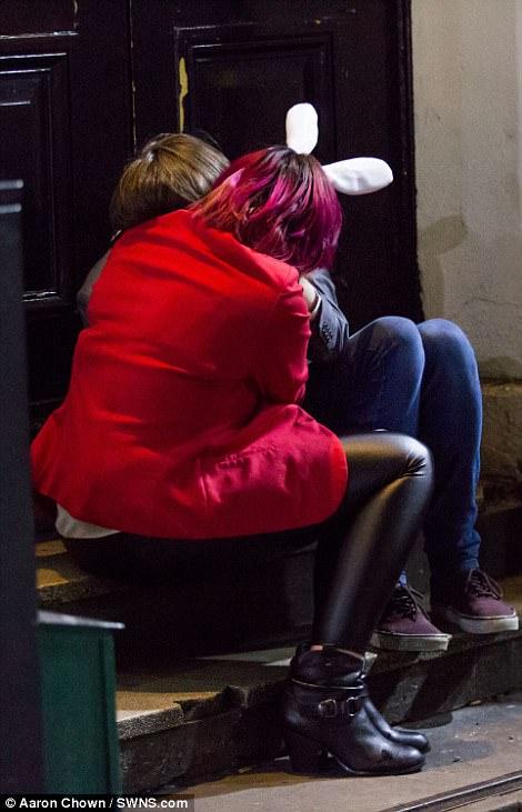 A woman in rabbit ears in Birmingham gets close to a friend