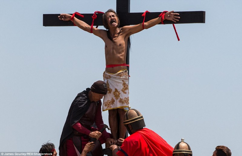 An act of penitence: A man in the Philippines screams as his feet and hands are nailed to a wooden cross as part of Easter celebrations to honour the suffering of Christ