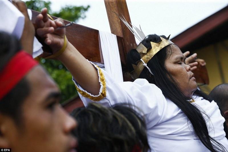 Precy Valencia is nailed to a cross in the Philippine capital of Manila as a sign of her faith and to seek forgiveness for her sins