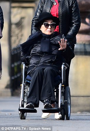 Ono looks down at her hand as she is pushed through Central Park