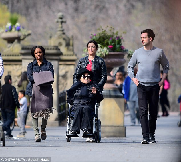 The 83-year-old wife of the late Beatle John Lennon flashed a smile alongside a young man (right) and two assistants (left and center), who pushed her around in a wheelchair