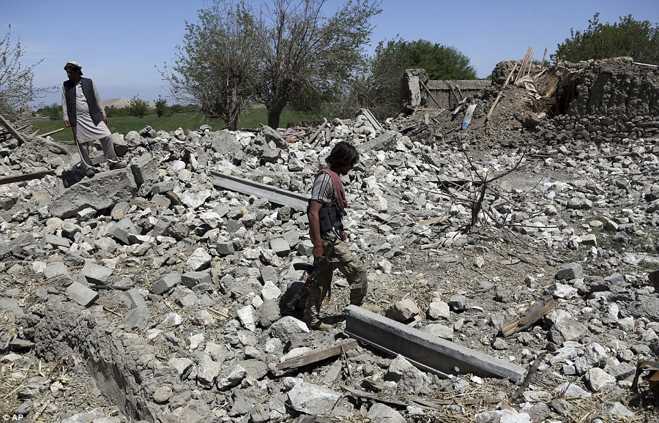Security police walks at the destroyed house after an operation in Asad Khil near the site of a U.S. bombing in the Achin district of Jalalabad, east of Kabul, Afghanistan