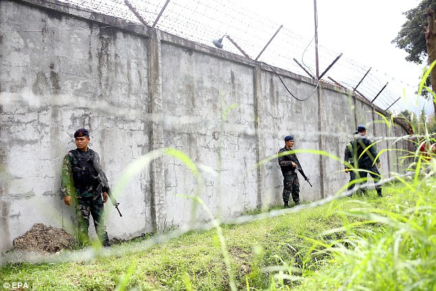 Most drug suspects in his precinct are shot by rookie cops who are either eager for the experience or nominated by their superiors, the commander said. Pictured, armed Filipino policemen stand guard next to the wall of a prison facility