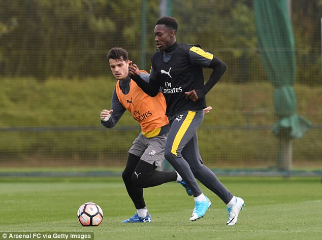 Welbeck carries the ball forward and away from the lurking Granit Xhaka