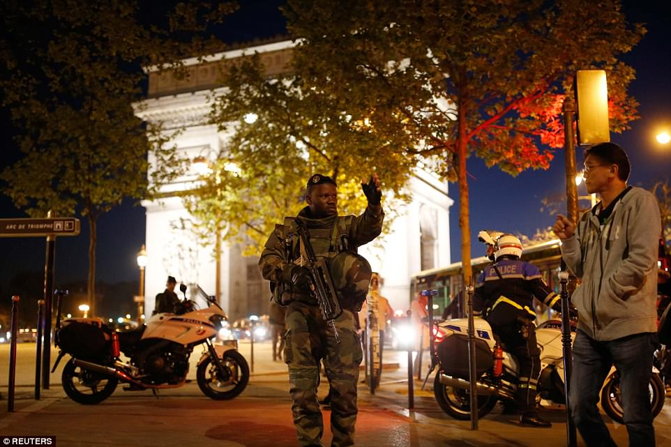 An armed soldier spoke to a man a told him to leave the area following the fatal shooting close to the Arc de Triomphe (pictured)
