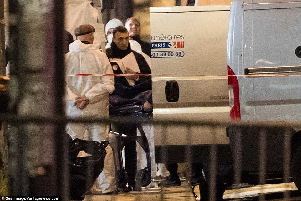 A body is removed from the scene after a traffic officer was killed by an ISIS gunman in central Paris last night