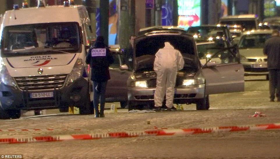 A still image from video footage shows police forensic investigators inspect the car used by the attacker in Paris last night