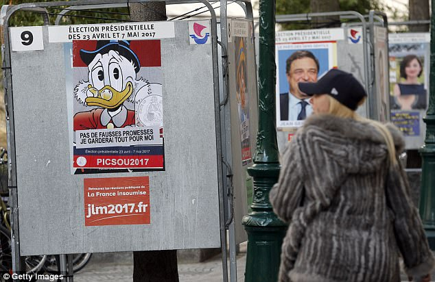 "A woman looks at a poster with the Disney character Uncle Scrooge fixed over the official poster of French presidential election candidate for the far-left coalition ""La France insoumise"" Jean-Luc Melenchon"
