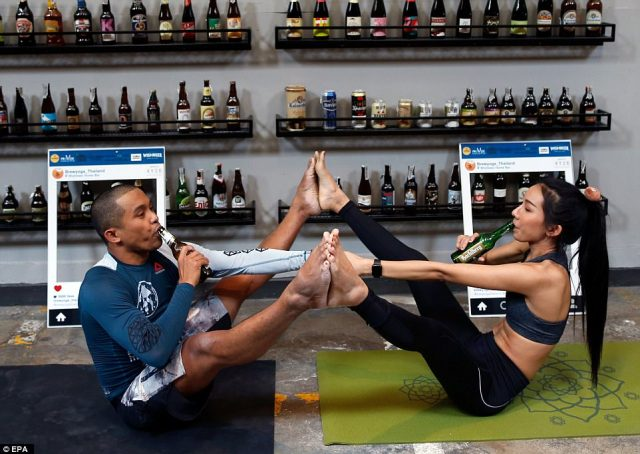 TwoThai yoga instructors indulge in a sip of beer while connecting their hands and feet in a mind-bending pose
