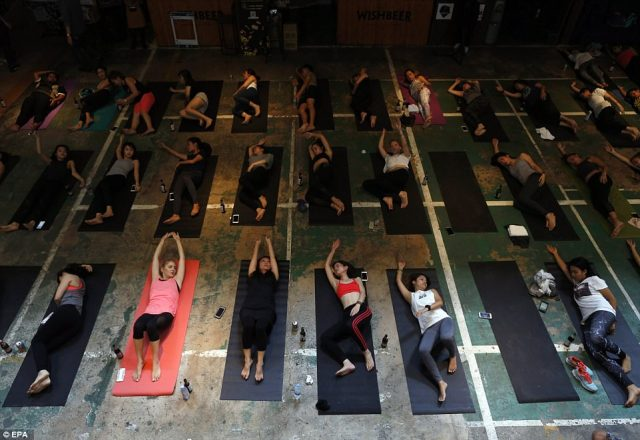 But the booze didn't always play an active role in the yoga - this photo shows attendees placing their beer bottles on the ground as they stretch out on their mats