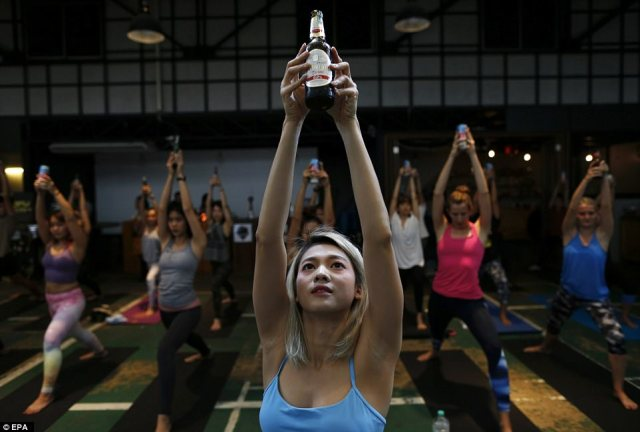 One class sees a group of women holding their beer bottles above their heads during a sun salutation