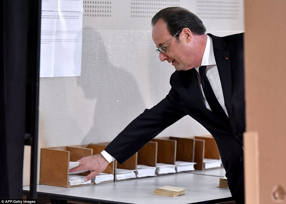 Outgoing French president Francois Hollande picks up ballot papers before casting his vote at a polling station in Tulle, central France, on April 23, 2017, during the first round of the Presidential election