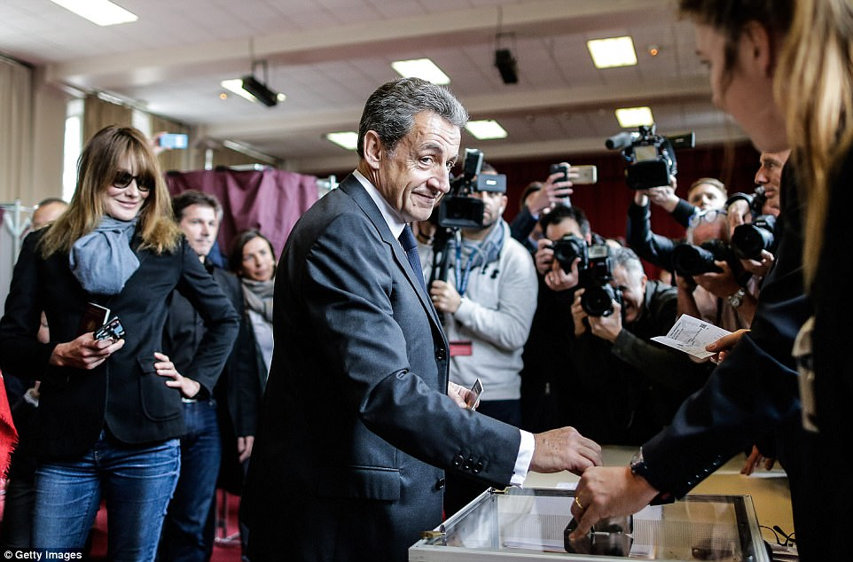 Former French President and former Head of Les Republicains right wing Party Nicolas Sarkozy (centre) and his wife, the singer Carla Bruni Sarkozy (left) vote in the first round of the 2017 French Presidential Election at the Jean de la Fontaine High School in the 16th arrondissement on April 23, 2017 in Paris, France