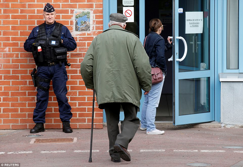 A policeman secures the entrance of a polling station as people arrive to vote in the first round of 2017 French presidential election in Henin-Beaumont, France, April 23, 2017