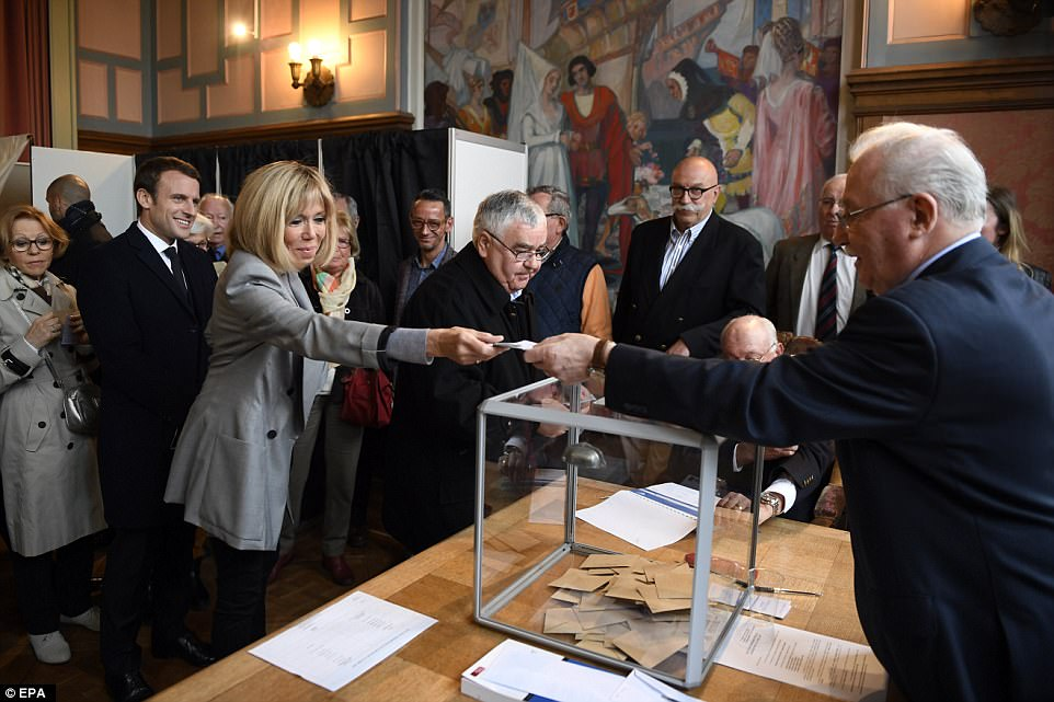 Brigitte Trogneux casts her ballot next to her husband, French presidential election candidate for the En Marche movement Emmanuel Macron during the first round of the Presidential election at a polling station in Le Touquet