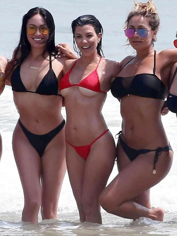 A size too small: Kourtney Kardashian seemed proud of her very tiny bikini - despite the fact it barely covered her chest - while posed with Stephanie Shepard (l) and a friend (right)