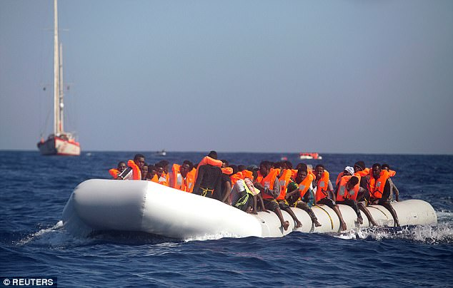 A dinghy overcrowded by African migrants and heading for Italy is seen drifting off the Libyan coast in August last year FILE PHOTO