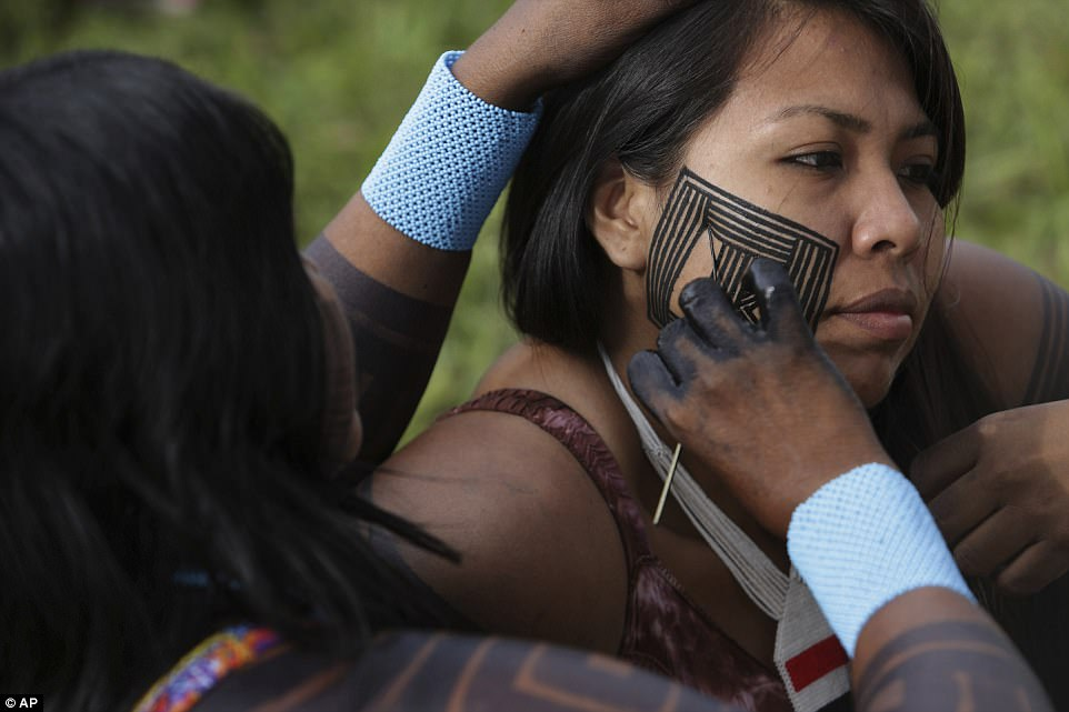 A Kayapo paints the face of her daughter during an assembly in Brasilia. The march has brought together several tribes to demand education and health