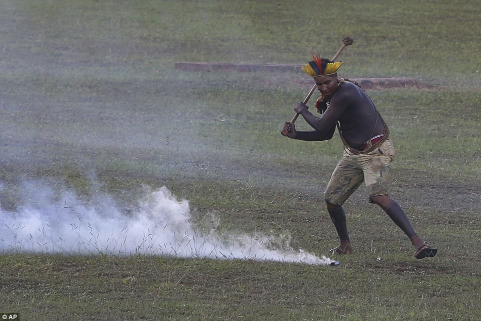 An indigenous man returns a tear gas canister to police. Sonia Guajajara, a coordinator for the march, said some 4,000 indigenous people and supporters took part in the protest