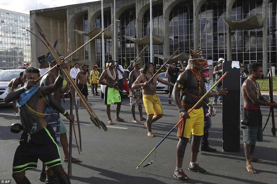 An indigenous man aims his arrow at police outside the National Congress, alongside fellow members of tribes who have united for the march