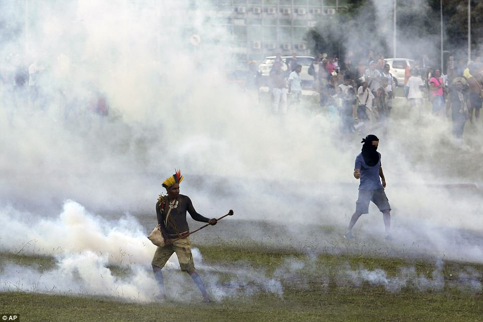 An indigenous man, left, stands amid tear gas fired by police. The tribes have said there will be a week ofactivities in the capital highlighting the tribes' many problems