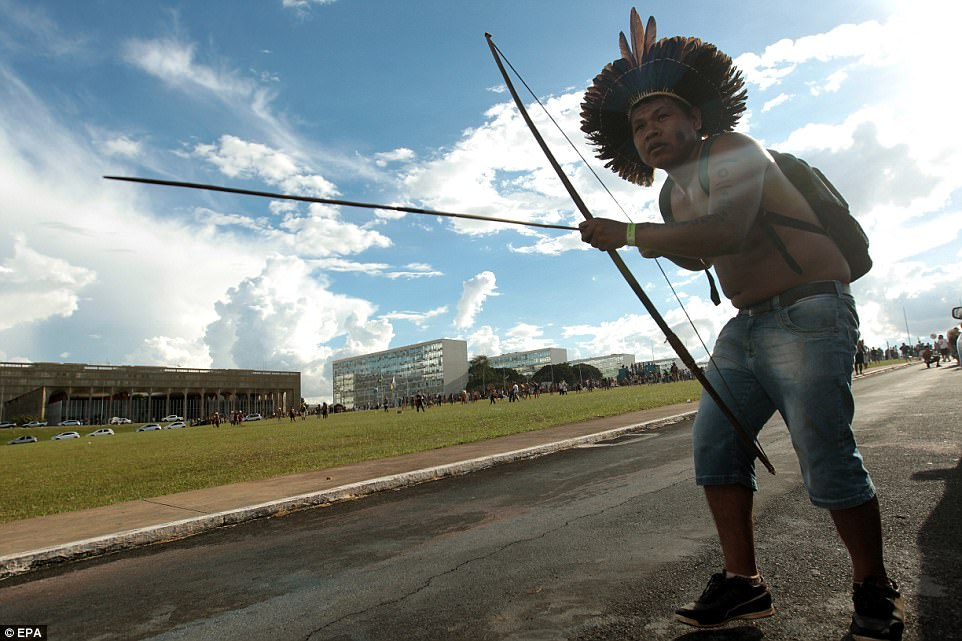A Brazilian indigenous person with a bow and arrow, dressed in traditional headdress. The protests carried on until the sun began to set over the capital city
