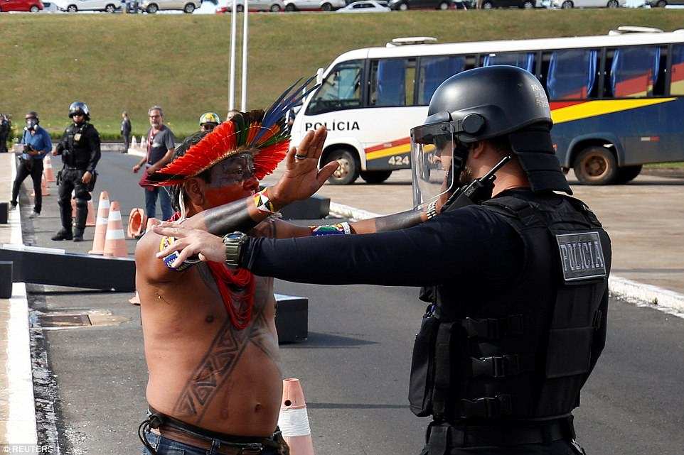 A Brazilian Indian in traditional headdress, appears to hold his hands in surrender to police as he confronts him during riots
