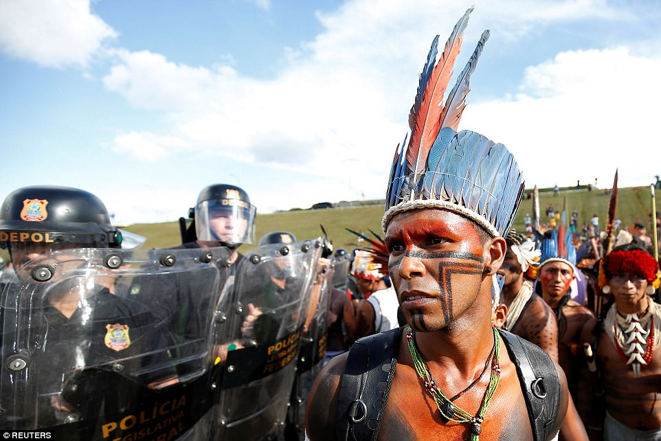 Lines of police form a blockade against the rows of thousands of indigenous people as they rally outside Brazil's national congress