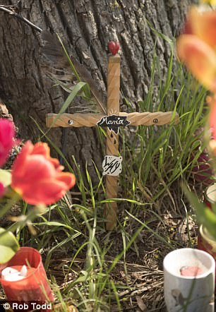 A simple cross sits among tulips at the murder site where 'Maria' was killed