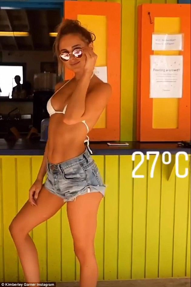Poser: The leggy blonde stood proudly, flaunting her taught abs and endless pins in a busty white bikini top and tiny denim shorts, her tresses swept on top of her head