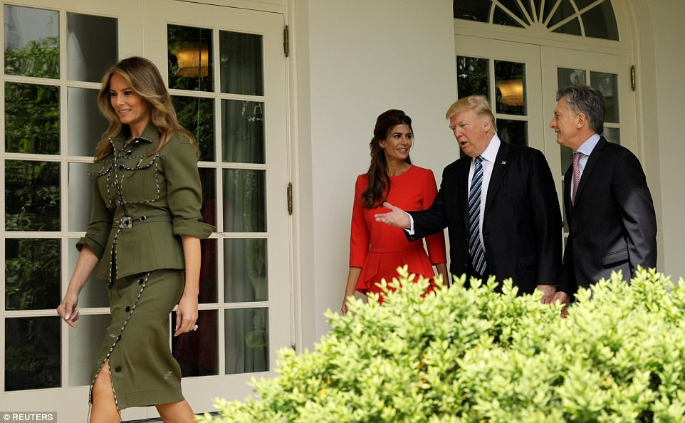 Trump is pictured speaking with their guests in the Colonnade as Melania led the way in her olive green suit