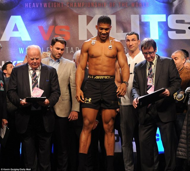 Joshua is all smiles as he glances down at his weight while Klitschko stands waiting in the background