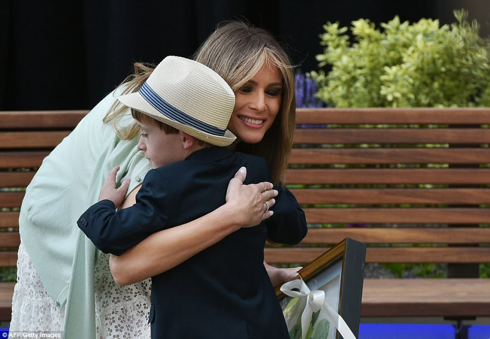 The First Lady hugs a boy who presented her with a gift during the ceremony. She quietly visited the garden for the first time back in March